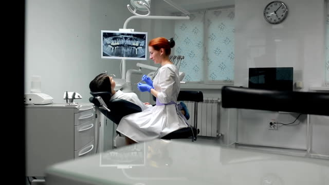 Female doctor in blue gloves and a white coat approaches to the chair of the patient and using x-ray and instruments the dentist inspects the teeth in the oral cavity. Girl patient video