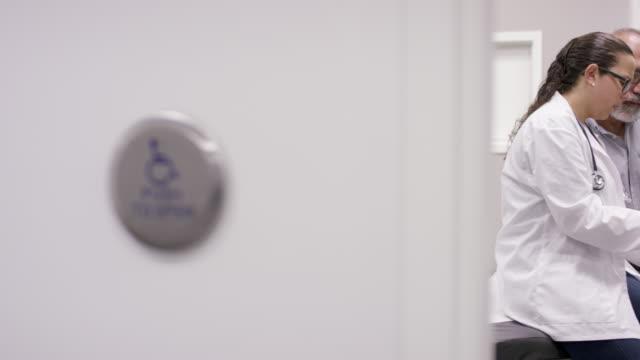 vídeos de stock, filmes e b-roll de doutor fêmea na consulta com o homem adulto maduro - questionário