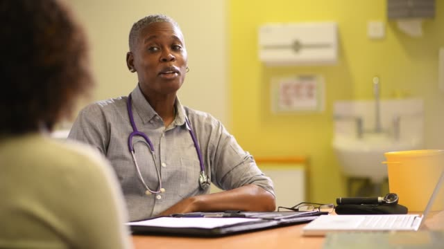female doctor in patient consultation a female doctor chats to a senior patient as a nurse preps medical equipment general practitioner stock videos & royalty-free footage
