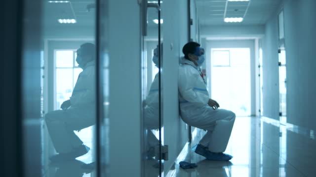 Female doctor is having a break on the floor in the corridor video