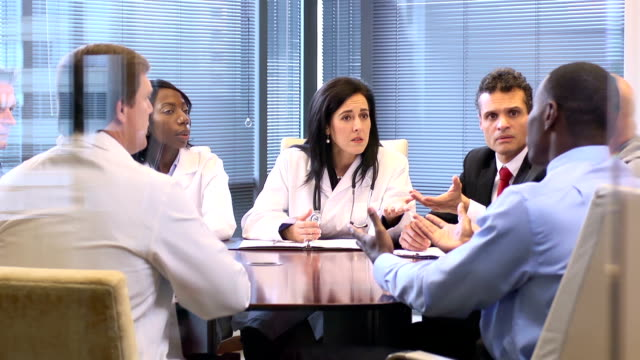 female doctor leads a meeting with professionals - ws - manager stock videos and b-roll footage
