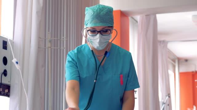female doctor making diagnostic procedure via phonendoscope. - stetoscopio video stock e b–roll