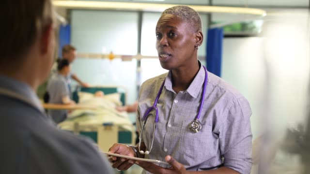 female doctor on the ward female doctor on the ward chatting to a nurse colleague nhs stock videos & royalty-free footage