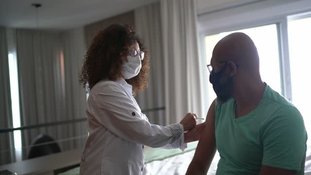 Female doctor or nurse vaccinating a man at home - wearing face mask Female doctor or nurse vaccinating a man at home - wearing face mask covid 19 vaccine stock videos & royalty-free footage
