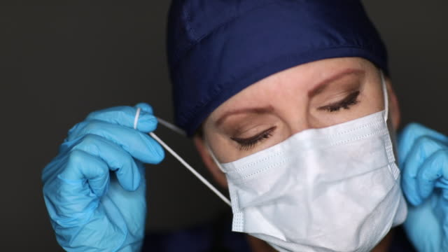 female doctor or nurse wearing medical face mask then taking it off of her face. - rimuovere video stock e b–roll