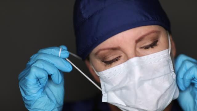 vídeos de stock e filmes b-roll de female doctor or nurse wearing medical face mask then taking it off of her face. - remover