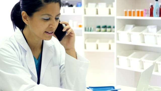 Female doctor or pharmacist uses smart phone and laptop at work Confident mid adult Asian female doctor or pharmacist uses a smart phone and laptop at work. Handheld camera pans from the laptop up to the woman talking on the smart phone. A pill counter and mortar and pestle are on the desk. pharmacist stock videos & royalty-free footage