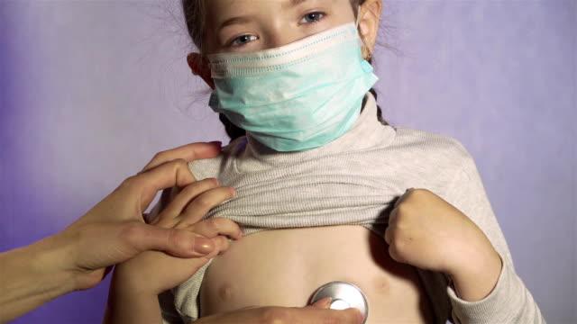 Kvinnlig läkare barnläkare med stetoskop lyssna hjärta eller lungor av glad friska söt flicka patient i skyddande mask vid läkarbesök på sjukhus närbild video