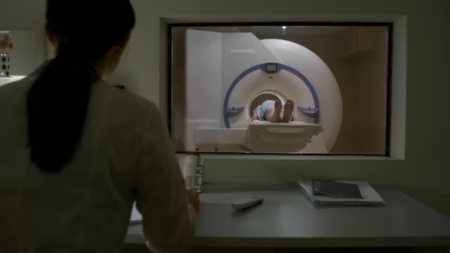 Bидео Female Doctor Performing MRI Scan