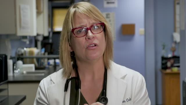 kvinnlig läkare som utför telemedicin lyssnar på en patient på sin klinik - videor med medicinsk undersökning bildbanksvideor och videomaterial från bakom kulisserna