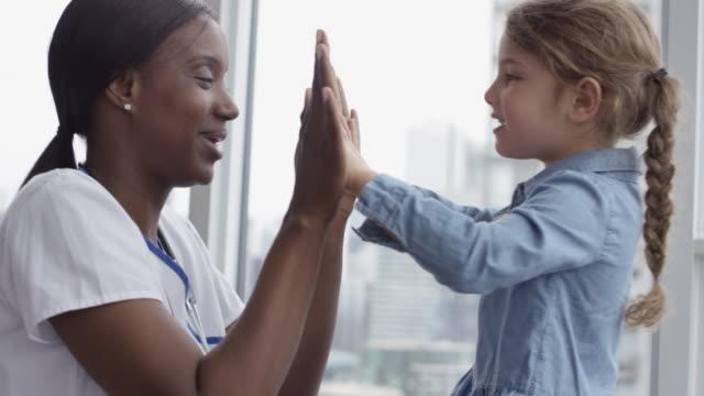 vidéos et rushes de docteur féminin jouant avec le patient d'enfant - enfant d'âge pré scolaire