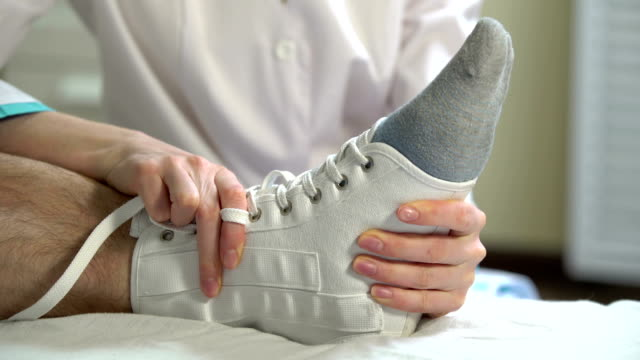 Female doctor puts a tight bandage on the injured ankle of the patient. Close-up. video