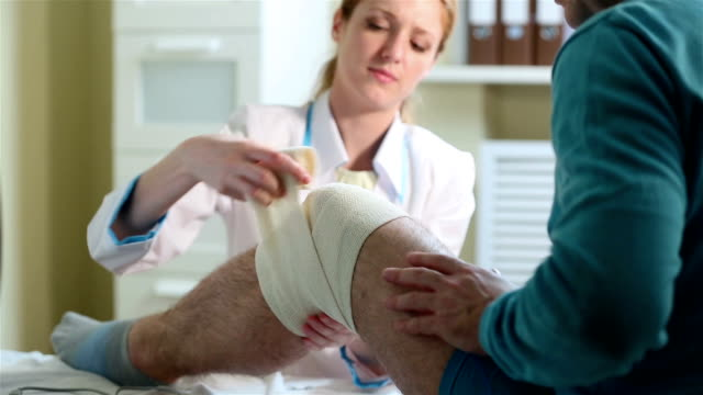 Female doctor puts a tight bandage on the injured knee of the patient. video