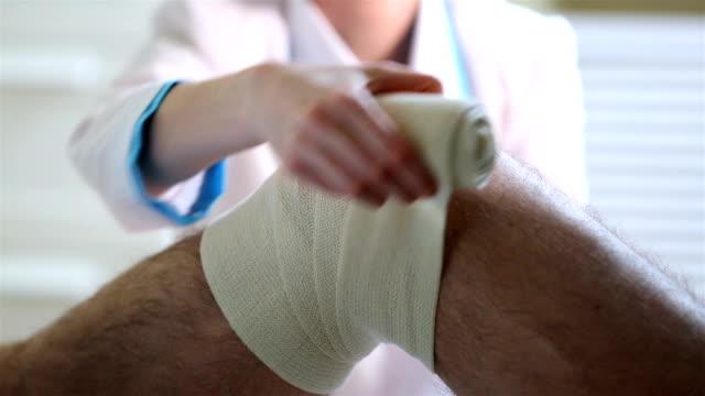 女医により、厳格なバンデージは、患者の負傷した膝。クローズアップます。 ビデオ