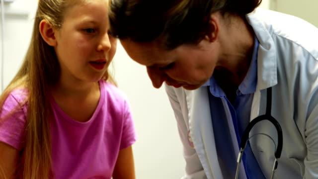 Female doctor putting bandage on injured leg of girl video
