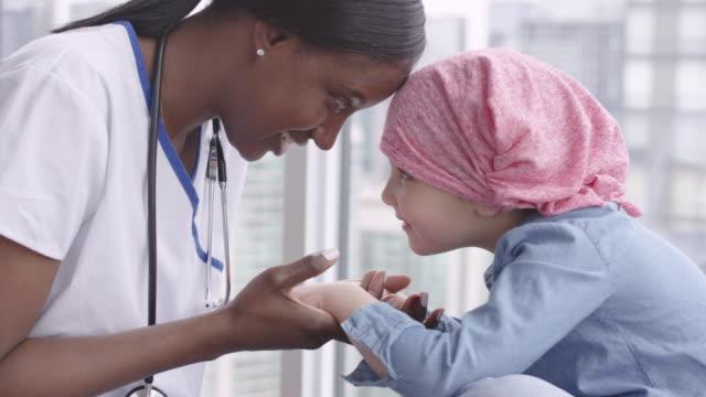 女性医師は、がんと闘う小児患者と座る - 回復点の映像素材/bロール