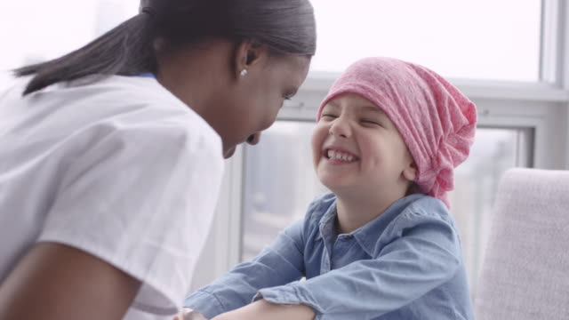 Female doctor sits with child patient fighting cancer A black doctor sits on the floor with her patient. The patient is a caucasian girl with cancer. The girl is wearing a scarf on her head. The doctor is talking and holding the girl's hands. The child is smiling up at the doctor and listening intently. cancer patient stock videos & royalty-free footage