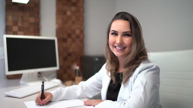 vídeos y material grabado en eventos de stock de doctor femenino sentado en el escritorio en la clínica - ortodoncista