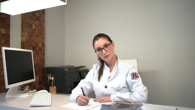 Female doctor sitting at desk in clinic Healthcare and Medicine dermatology stock videos & royalty-free footage