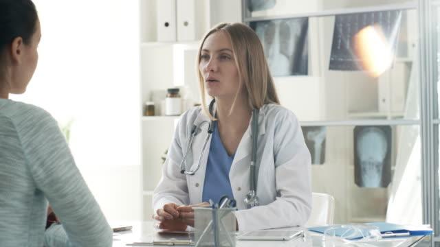 女性医師のクリニックでは、患者に話す - 処方箋点の映像素材/bロール
