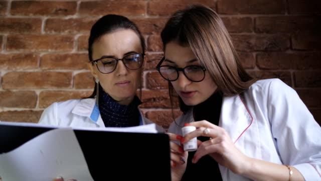 stajyer kız için hastanın tanı hakkında konuşan kadın doktor. kız stajyer paketi hapları ile ek açıklamayı okuyun. - vitamin d stok videoları ve detay görüntü çekimi
