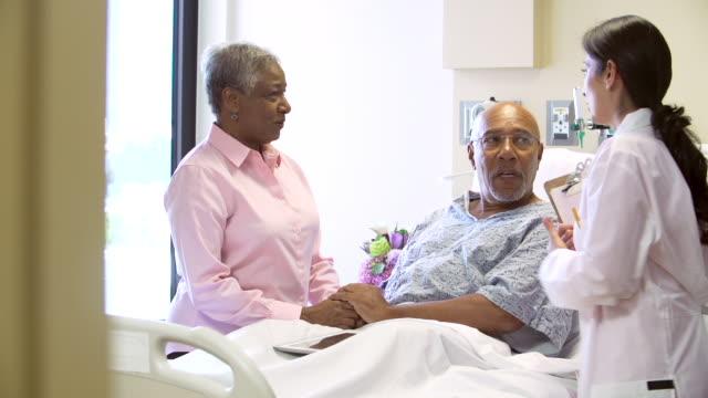 female doctor talking to senior couple in hospital room - ziyaret stok videoları ve detay görüntü çekimi