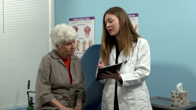 Female doctor talking to senior patient. video