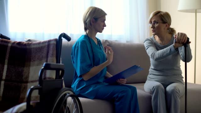 female doctor talking to senior woman at hospital, making notes, rehabilitation - ассистент стоковые видео и кадры b-roll