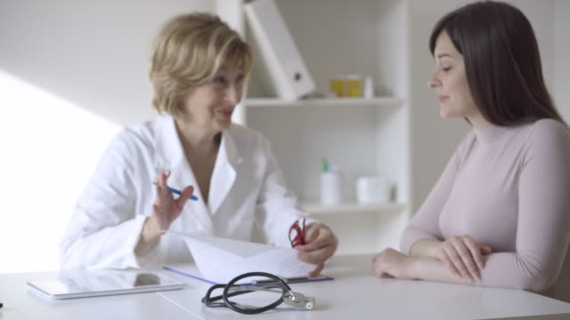Female doctor talking with patient video
