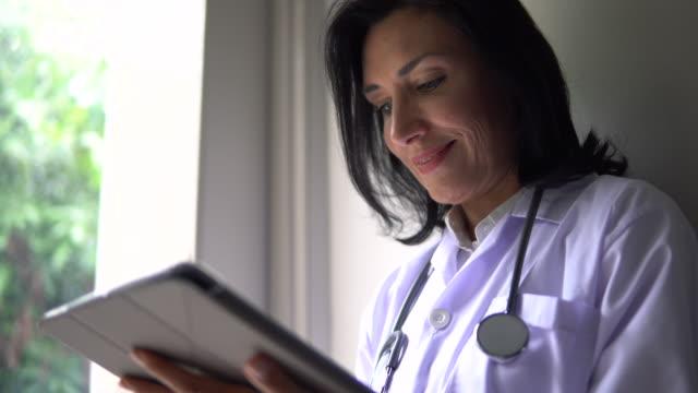 kvinna läkare använda digitala surfplatta med stetoskop - videor med medicinsk undersökning bildbanksvideor och videomaterial från bakom kulisserna