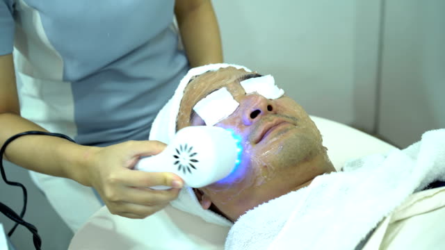 4k female doctor using ipl blue light to sterilize acne on young male face at beauty clinic - depilacja filmów i materiałów b-roll