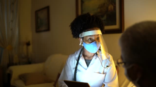 Female doctor visiting her patient at his home - appointment with digital tablet video