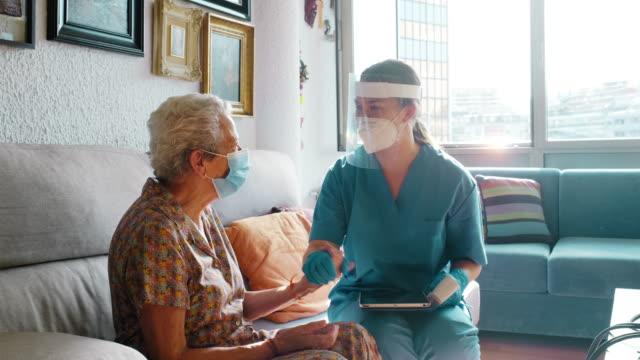 bir kadın doktor huzurevinde yaşlı bir kadını ziyaret ediyor. - ziyaret stok videoları ve detay görüntü çekimi