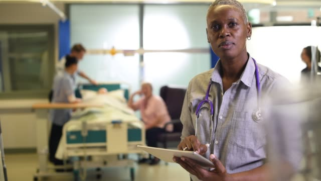 female doctor with tablet female doctor on the ward chatting to a nurse colleague nhs stock videos & royalty-free footage