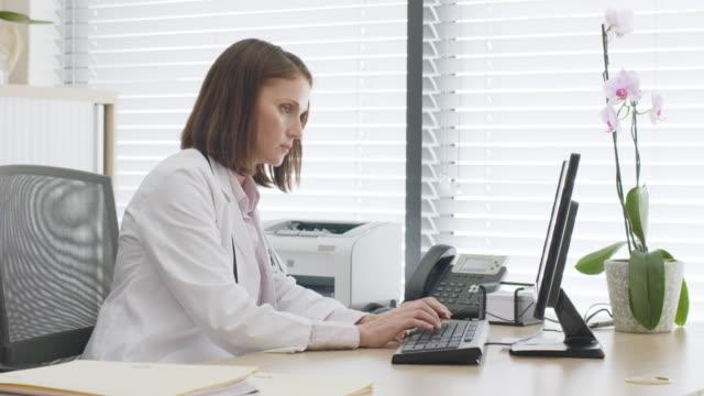 female doctor working on computer at desk - komputer filmów i materiałów b-roll