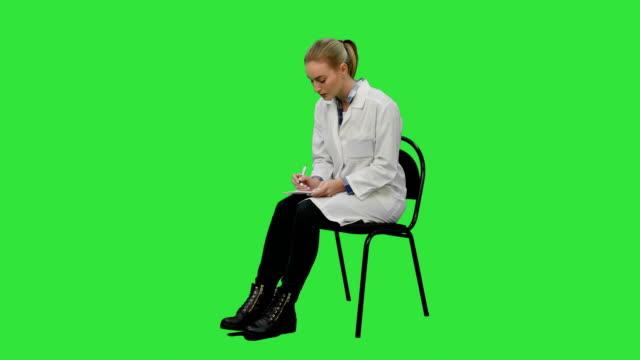 kvinnliga läkare skriva recept på en patient på en grön skärm, chroma key - sitta bildbanksvideor och videomaterial från bakom kulisserna