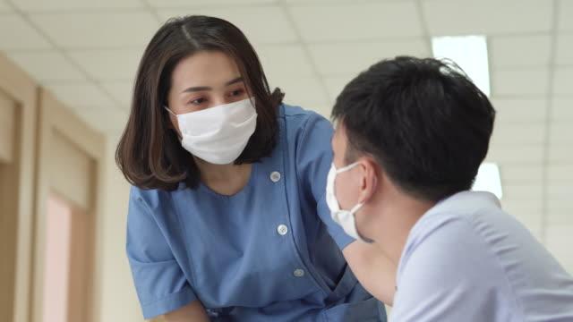 kvinnliga läkare ger uppmuntran till manliga patienter på sjukhuset. - face mask bildbanksvideor och videomaterial från bakom kulisserna
