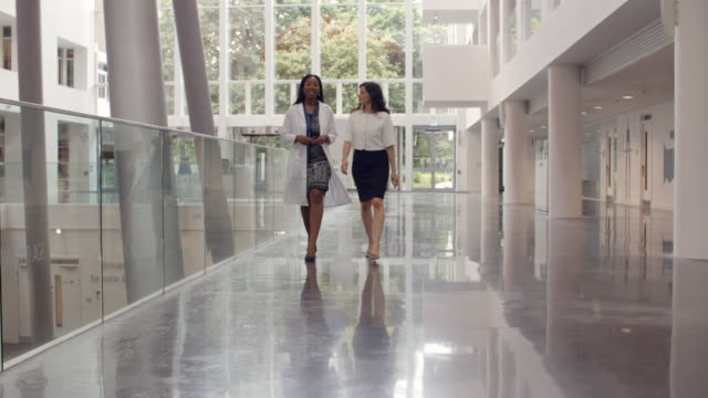 Female Doctors Talking As They Walk Through Hospital video