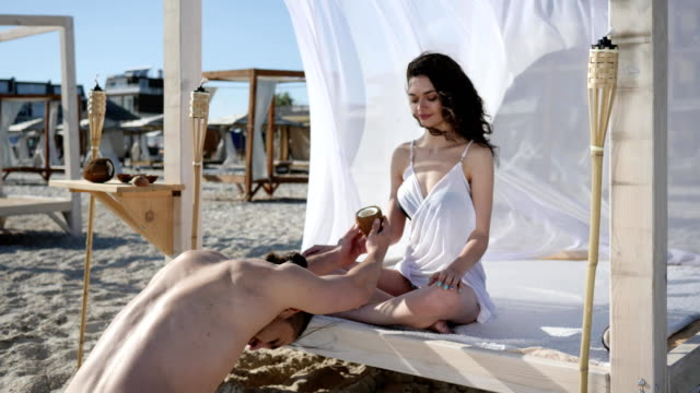 female Dreams on summer rest, sexy male presents in hand coconut drink girl, man with cocktail on tropical beach video