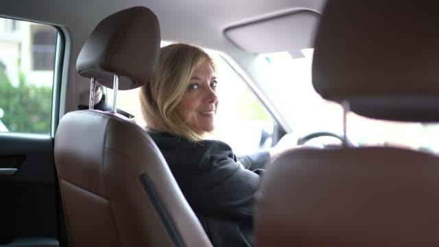 Conductor femenino mirando sobre el debe en la cámara - vídeo