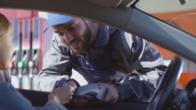 female driver paying at gas station through car window - credit card filmów i materiałów b-roll