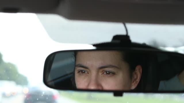 dikiz aynası ile görülen yolda kadın sürüş - ayarlamak stok videoları ve detay görüntü çekimi