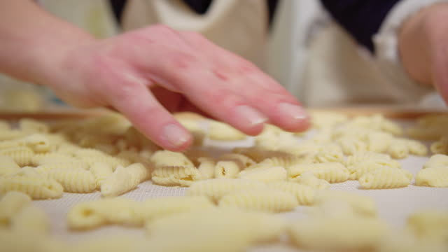 Female drying freshly made pasta on a drying tray