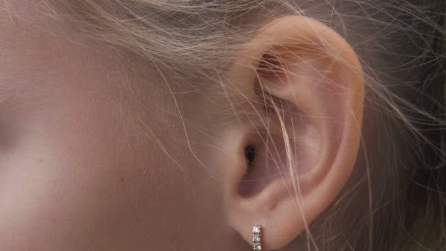 female ear with earring close up. ear of woman blonde with decorative piercing - orecchio umano video stock e b–roll