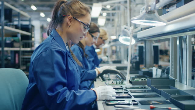 Female Electronics Factory Worker in Blue Work Coat and Protective Glasses is Assembling Printed Circuit Boards for Smartphones with Tweezers. High Tech Factory with more Employees in the Background.