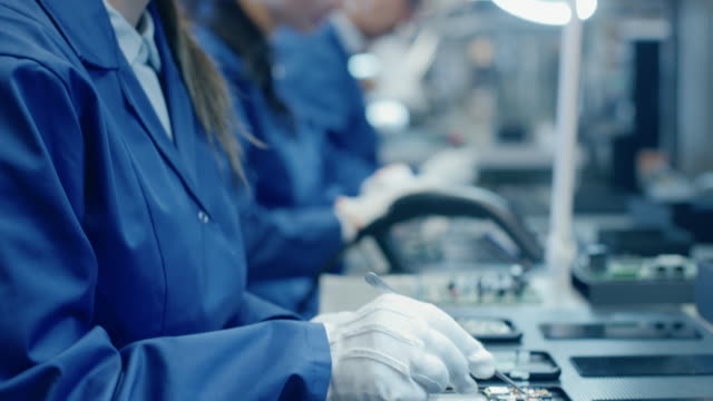 female electronics factory workers in blue work coat and protective glasses assembling printed circuit boards for smartphones with tweezers. high tech factory with more employees in the background. - produkować filmów i materiałów b-roll