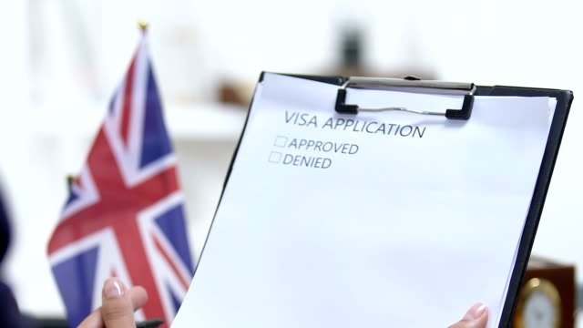 Female embassy worker checking United Kingdom visa application, marking denied Female embassy worker checking United Kingdom visa application, marking denied form filling stock videos & royalty-free footage