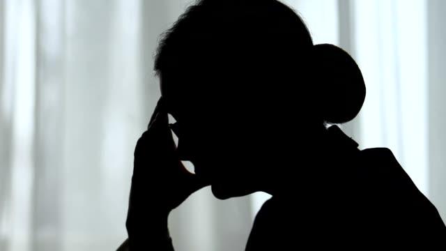 女性社員が頭を抱え、片頭痛やうつ病、過労 - 悩む点の映像素材/bロール