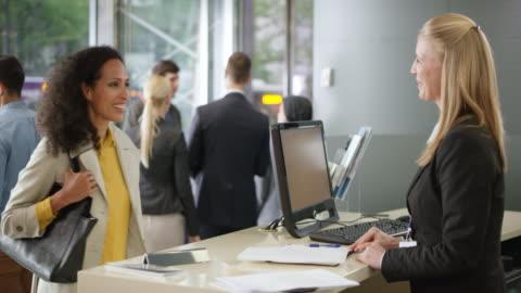 vidéos et rushes de employée à aider un client en lui donnant un dépliant et une explication - client