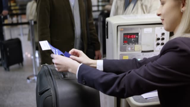 Female employee placing a bag tag on a luggage of a senior couple checking in at the airport video